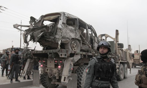 A U.S. military wrecker carries away a vehicle that was destroyed in a suicide car bomb attack on the Jalalabad-Kabul road in Kabul, Afghanistan, Friday, Dec. 27, 2013. The U.S.-led coalition in Afghanistan says several service members were killed Friday