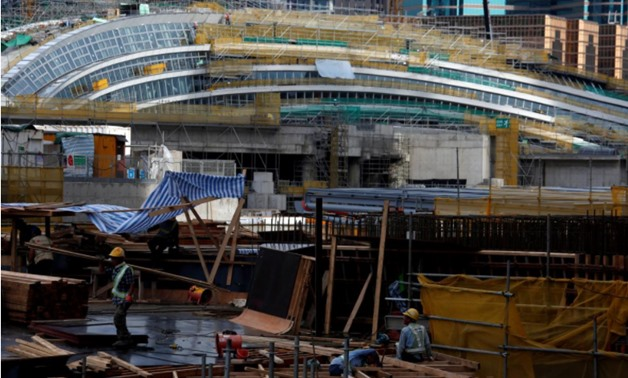 Laborers work in front of West Kowloon Terminus, under construction for the Guangzhou-Shenzhen-Hong Kong Express Rail Link, in Hong Kong, China July 21, 2017. Picture taken July 21, 2017 - REUTERS/Bobby Yip/File Photo