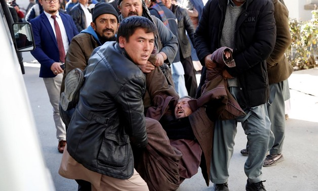 People carry a mourning man at a hospital after a suicide attack in Kabul, Afghanistan December 28, 2017. REUTERS/Mohammad Ismail