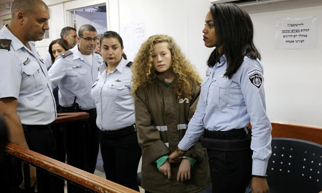 Palestinian teen Ahed Tamimi enters a military courtroom escorted by Israeli Prison Service personnel at Ofer Prison near the West Bank city of Ramallah, December 28, 2017. REUTERS/Ammar Awad