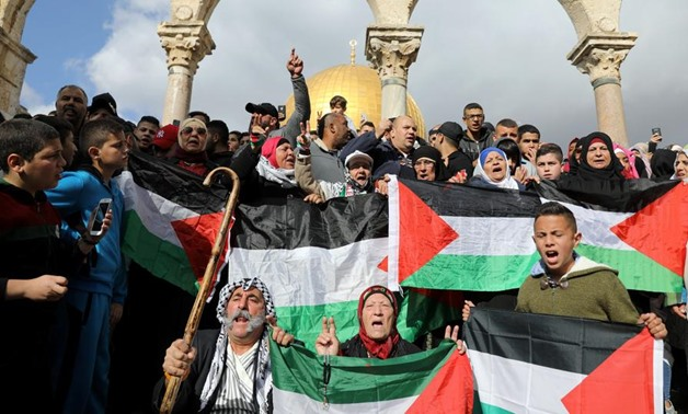 "Worshippers hold Palestinian flags as they protest after Friday prayers on the compound known to Muslims as Noble Sanctuary and to Jews as Temple Mount in Jerusalem's Old City, as Palestinians call for a ""Day of Rage"" in response to President Donald Trump"