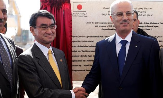 Japanese Foreign Minister Taro Kono (C-L) shakes hands with Palestinian prime minister Rami Hamdallah in the West Bank city of Jericho on December 26, 2017- AFP