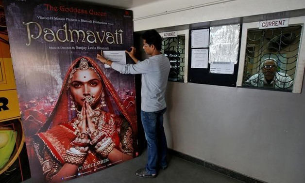 "FILE PHOTO: A worker tapes a message in support of the release of the upcoming Bollywood film ""Padmavati"" on its poster at a ticket selling counter in a cinema hall in Kolkata, India, November 28, 2017. REUTERS/Rupak De Chowdhuri"