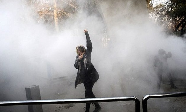A woman raises her fist amid tear gas at the University of Tehran during a protest on December 30, 2017 - AFP