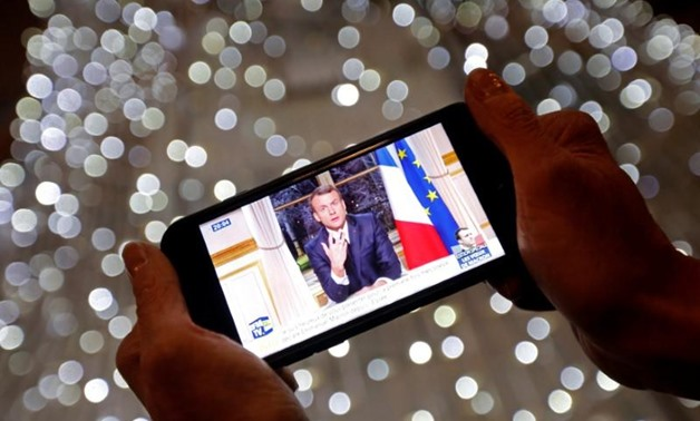 French President Emmanuel Macron is seen on the screen of an iPhone in Marseille, as he gives the traditional New Year speech during a prime time news broadcast at the Elysee Palace in Paris, France, December 31, 2017. REUTERS/Jean-Paul Pelissier