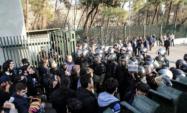 Students scuffle with police at the University of Tehran during a demonstration driven by anger over economic problems in the Iranian capital Tehran on December 30, 2017 - AFP