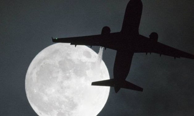 "Justin Tallis, AFP | A plane flys in front of a ""super moon"" or ""wolf moon"" on its approach to London Heathrow Airport on January 1, 2018."