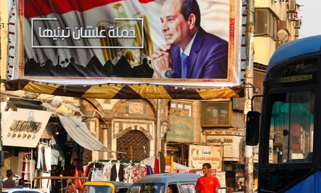 "People walk near a poster of Egyptian President Abdel Fattah al-Sisi of the campaign titled, ""Alashan Tabneeha"" (So You Can Build It), Egypt, October 17, 2017 – Reuters"