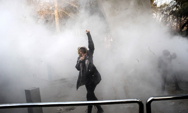 An Iranian woman raises her fist amid the smoke of tear gas at the University of Tehran during a protest driven by anger over economic problems, in the capital Tehran on December 30, 2017. – AFP