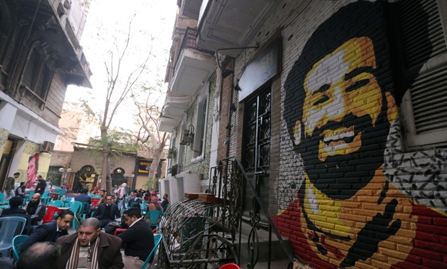A mural of Egypt and Liverpool soccer star Mohamed Salah is seen as people sit outside a coffee shop in Cairo, Egypt, January 4, 2018 - REUTERS/Mohamed Abd El Ghany