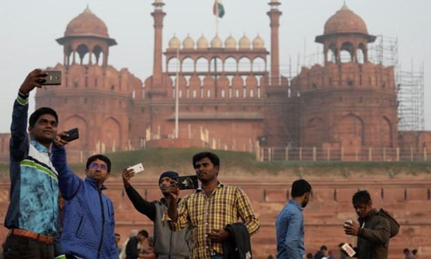 Domestic tourists take selfies in front of the historic Red Fort, one of the tourist destinations in the old quarters of Delhi, India, January 3, 2018.