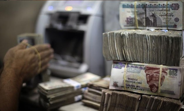 An employee counts money at an exchange office in downtown Cairo June 5, 2014 - REUTERS/Amr Abdallah Dalsh