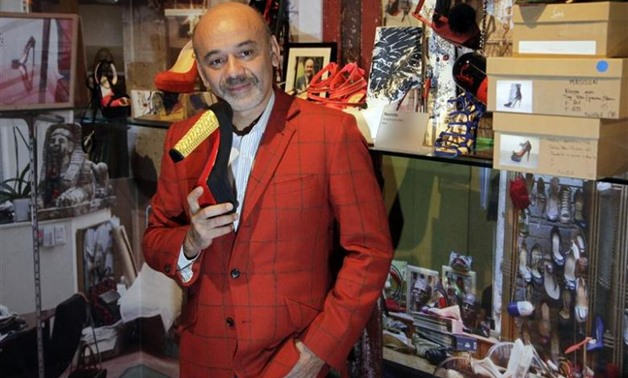 French shoe designer Christian Louboutin poses for photographs during a media viewing of his retrospective exhibition at the Design Museum in London, April 30, 2012 - REUTERS/Stefan Wermuth
