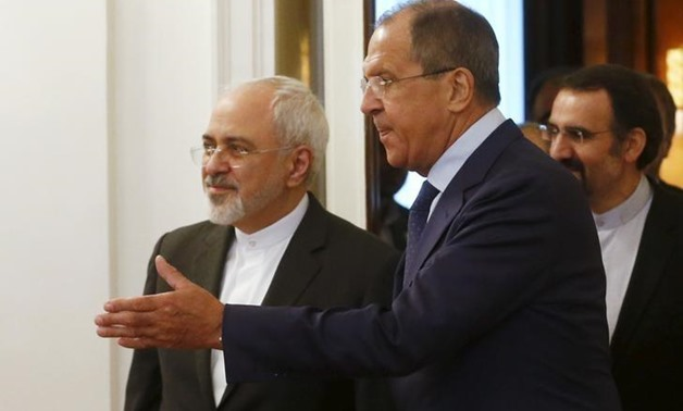 Russian Foreign Minister Sergei Lavrov (R) shows the way to his Iranian counterpart Mohammad - Reuters