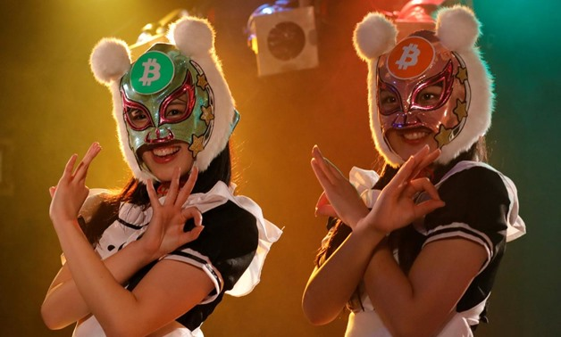 "Members of Japan's idol group ""Virtual Currency Girls"" wearing cryptocurrency-themed masks pose after performing in their debut stage event in Tokyo, Japan, January 12, 2018. REUTERS/Kim Kyung-Hoon"