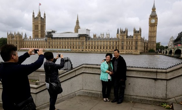 Chinese tourists take pictures near the Big Ben clock tower in London. ( Reuters)