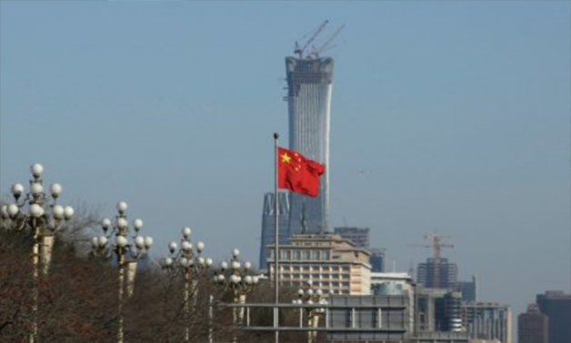 A Chinese flag flutters at Xinhuamen Gate of Zhongnanhai leadership compound in central Beijing, China December 15, 2017. The construction site of China Zun, planned to be the tallest building in Beijing, is seen behind - REUTERS/Jason Lee/File photo