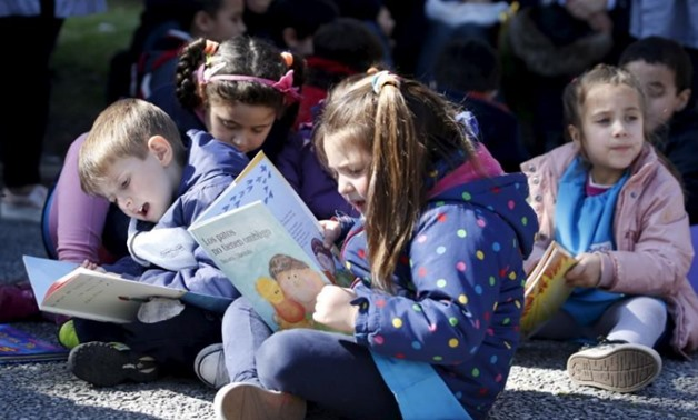 Children read books at Montevideo's Independencia square, September 4, 2015. REUTERS/Andres Stapff