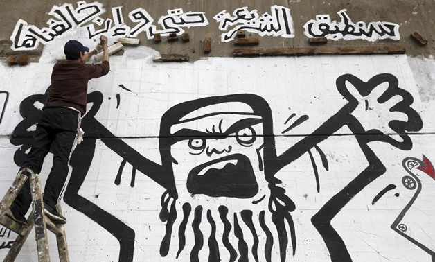 Man works on graffiti representing the Muslim Brotherhood along Mohamed Mahmoud street near Tahrir Square in Cairo, on January 24, 2013- REUTERS/Amr Abdallah Dalsh