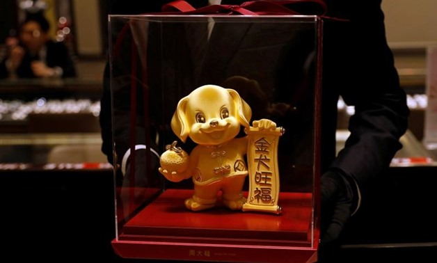 FILE PHOTO: A staff poses with a dog-shaped gold figurine, at Chow Tai Fook Jewellery store ahead of the Lunar Year of the Dog in Hong Kong, China December 14, 2017. REUTERS/Tyrone Siu/File Photo