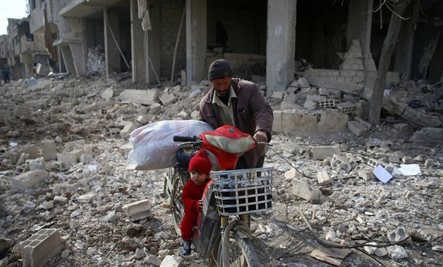 FILE PHOTO - A man is seen with a child who rides a bicycle inside damaged area in Misraba, Eastern Ghouta, near Damascus, Syria January 11, 2018 -  REUTERS/Bassam Khabieh