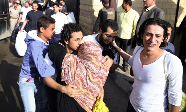 An Egyptian woman hugs a youth who was released from Cairo's Tora prison on November 18, 2016 - AFP