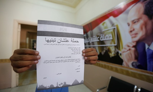 "A man hold a paper of ""To build it"" campaign to support President Sisi for another term- Egypt Today / Hassan Mohamed"