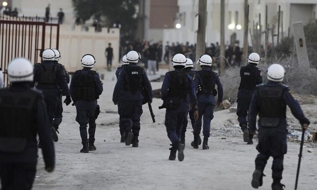 Riot police walk towards protesters during clashes in the village of Daih, west of Manama. REUTERS/Stringer
