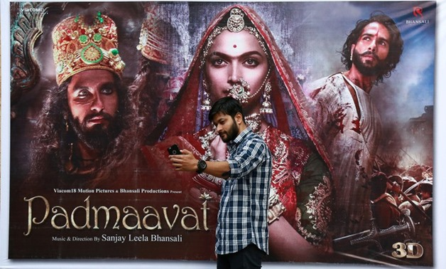 "A cinemagoer takes a selfie in front of a poster of Bollywood movie ""Padmaavat"" outside a movie theatre in Kochi, India, January 25, 2018. REUTERS/Sivaram V"