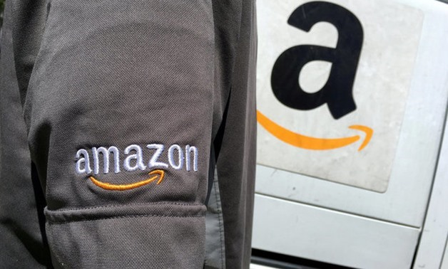 An Amazon.com Inc driver stands next to an Amazon delivery truck in Los Angeles - Reuters