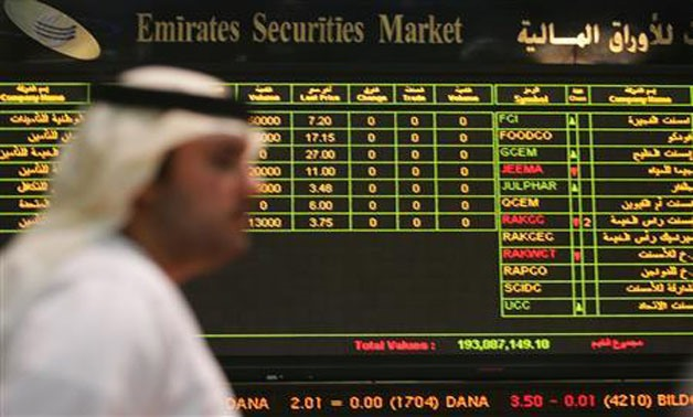 A file photo of a trader walking past the quotation board at the Abu Dhabi stock market, July 11, 2006 - Reuters/Ravindranath