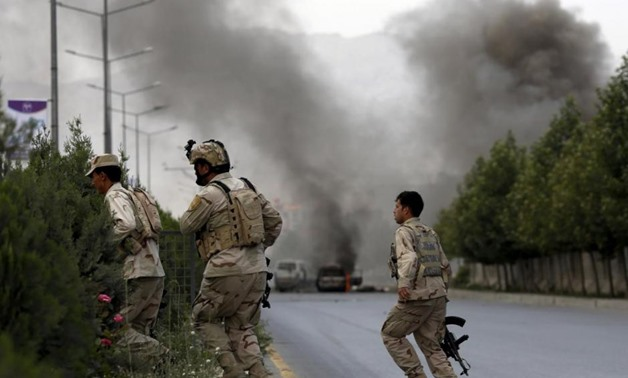 Members of Afghan security forces cross a road as smoke billows from the site of an attack near the Afghan parliament in Kabul, Afghanistan June 22, 2015.