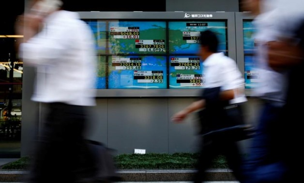 FILE PHOTO: People walk past an electronic board showing Japan's Nikkei average outside a brokerage at a business district in Tokyo, Japan August 9, 2017. REUTERS/Kim Kyung-Hoon