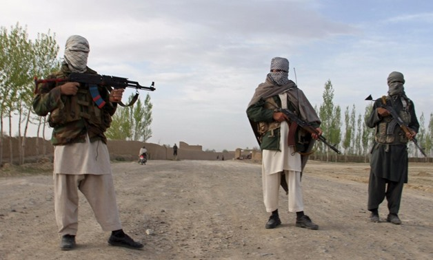 Members of the Taliban stand at the site of the execution of three men in Ghazni Province April 18, 2015 -  Stringer/REUTERS