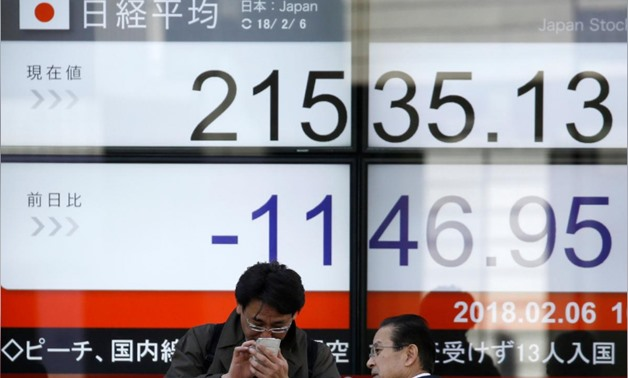 Men look at a mobile phone in front of an electronic board showing Japan's Nikkei average outside a brokerage in Tokyo, Japan, February 6, 2018. REUTERS/Toru Hanai