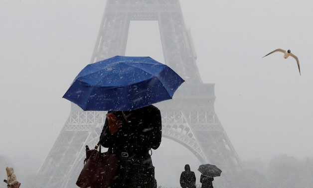 A woman holds an umbrella to protect herself from falling snow near the Eiffel Tower in Paris on Feb. 6, 2018. — Reuters