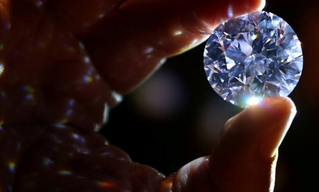 An assistant holds a 102.34 carat white diamond at Sotheby's auction house in London, Britain February 8, 2018. REUTERS/Hannah McKay