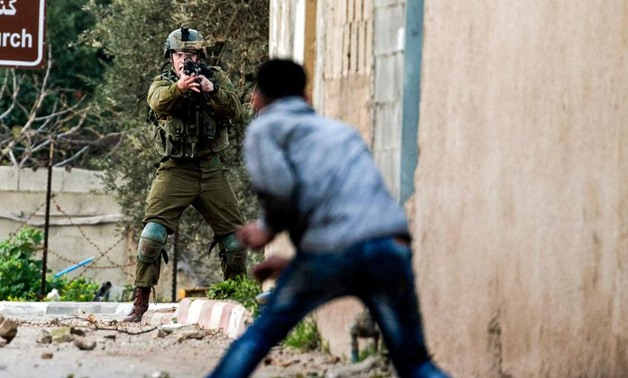 A Palestinian protester confronts an Israeli soldier during an army search operation in the Palestinian village of Burqa, about 18 kilometres northwest of Nablus in the occupied West Bank, on February 3, 2018. Jaafar Ashtiyeh / AFP