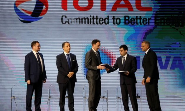 Lebanese Energy Minister Cesar Abi Khalil hands a document to Stephane Michel, Total's head of exploration and production in the Middle East and North Africa, during Lebanon's first offshore oil and gas contract ceremony in Beirut, Lebanon February 9, 201