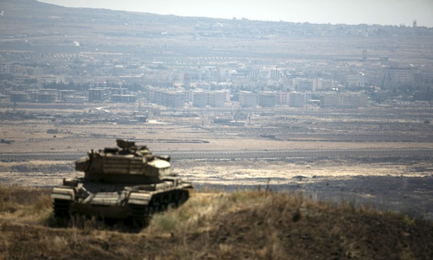 The Syrian area of Quneitra is seen in the background as an Israeli tank parks on a hill, near the ceasefire line between Israel and Syria, in the Israeli-occupied Golan Heights – REUTERS