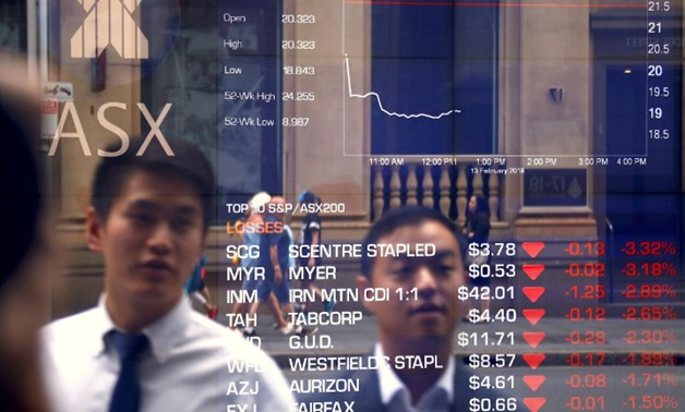 Pedestrians are reflected in a window displaying stock prices at the Australian Securities Exchange (ASX) in Sydney, Australia, February 13, 2018. REUTERS/David Gray