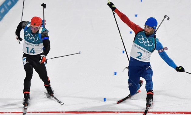 Biathlon Centre - Pyeongchang, South Korea - February 18, 2018 - Martin Fourcade of France and Simon Schempp of Germany finish. REUTERS/Toby Melville