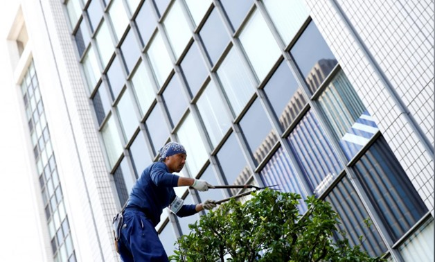 FILE PHOTO: A worker cuts a tree in front of an office building at a business district in Tokyo, Japan, May 18, 2016. REUTERS/Thomas Peter/File Photo
