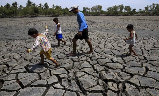 A father with his children walk over the cracked soil of a 1.5 hectare dried up fishery at the Novaleta town in Cavite province, south of Manila May 26, 2015. REUTERS/Romeo Ranoco/Files