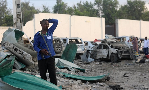 A security officer from Doorbin Hotel assesses the debris after a suicide car explosion in front of the hotel in Mogadishu, Somalia February 24, 2018 / Reuters