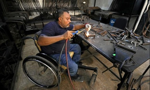 A disabled Egyptian man works in a workshop those manufactures products for the disabled in Cairo, Egypt 2017 - Reuters