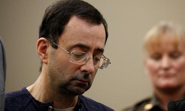FILE PHOTO: Larry Nassar, a former team USA Gymnastics doctor who pleaded guilty in November 2017 to sexual assault charges, stands with his legal team during his sentencing hearing in Lansing, Michigan, U.S., January 24, 2018. REUTERS/Brendan McDermid