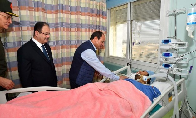 Egyptian President Abdel Fattah al-Sisi (3rd L) visits police officer Mohamed El-Hayes who was rescued after being kidnapped during an attack in the Western Desert, at a military hospital in Cairo, Egypt, November 1, 2017 in this handout picture courtesy