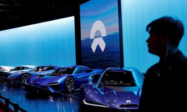 FILE PHOTO: A man is silhouetted in front of Nio cars at the auto show, in Shanghai, China April 20, 2017. REUTERS/Aly Song/File Photo