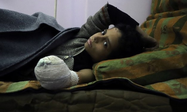 Syrian child Khaled al-Ghorani lies at a clinic in Eastern Ghouta on March 1, 2018 after his hand was amputated